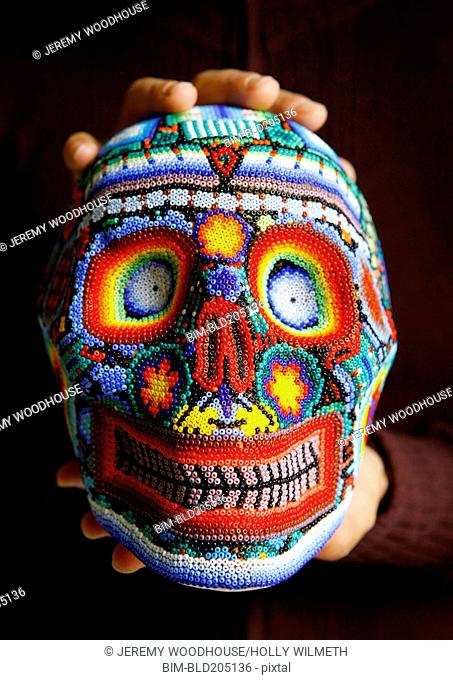 Caucasian hand holding colorful beaded skull