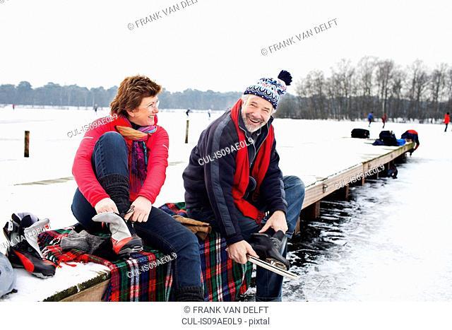 Couple sitting on pier putting on ice skates
