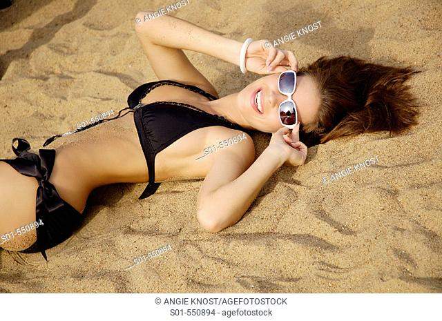 Attractive woman in bikini on beach.  She is holding sunglasses, smiling, and making eye contact with viewer as if greeting or posing