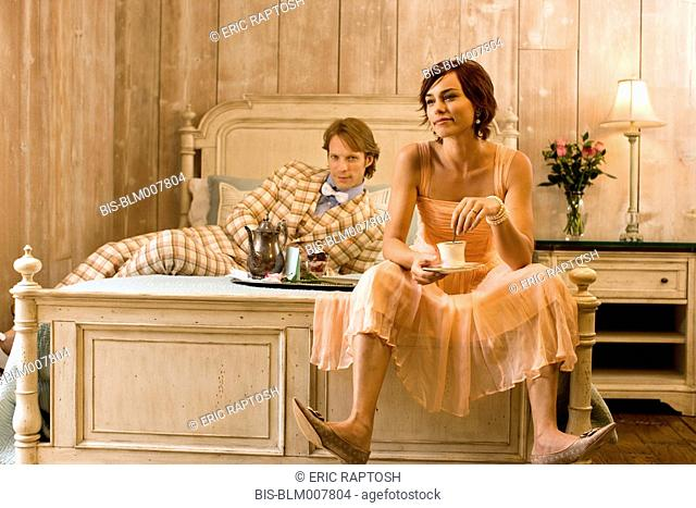 Elegant couple sitting on bed in evening clothes