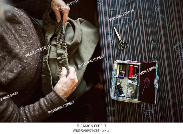 Senior woman with sewing kit, top view