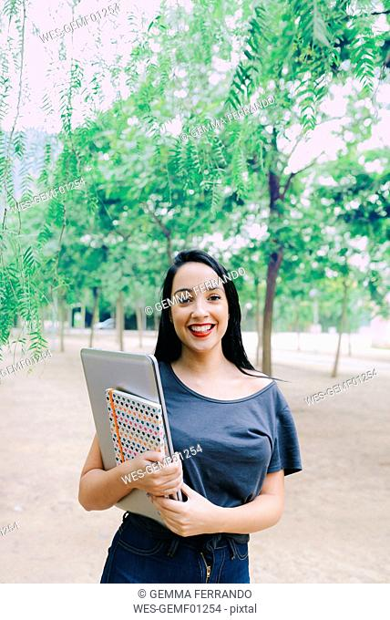 Smiling young woman holding a laptop and a notebook outdoors
