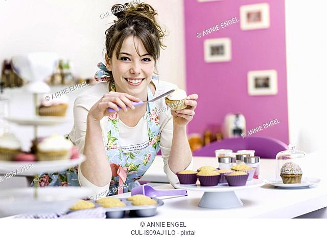 Woman decorating cupcake