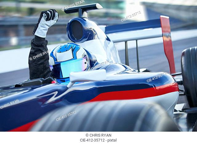 Portrait formula one race car driver wearing helmet and cheering with fist on sports track