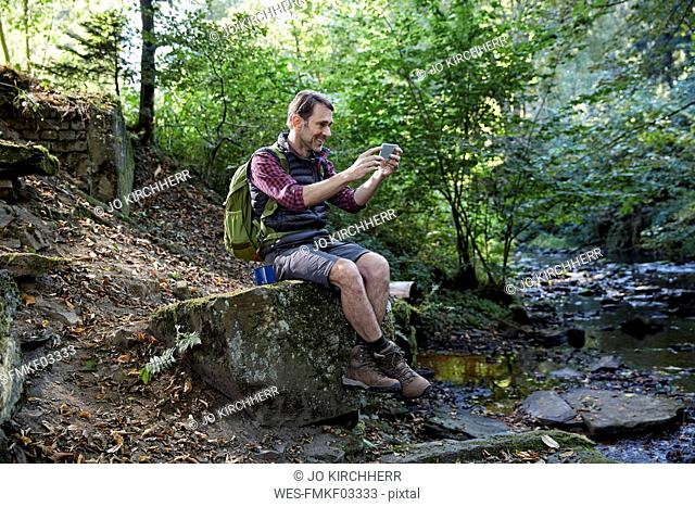 Hiker in forest sitting on rocks at a brook, taking selfie