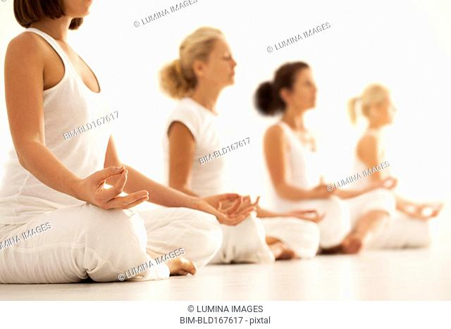 Close up of women meditating in yoga class