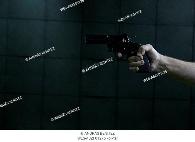 Hand of a man aiming with a revolver in an indoor shooting range