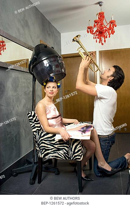 Woman drying hair and a man playing trumpet