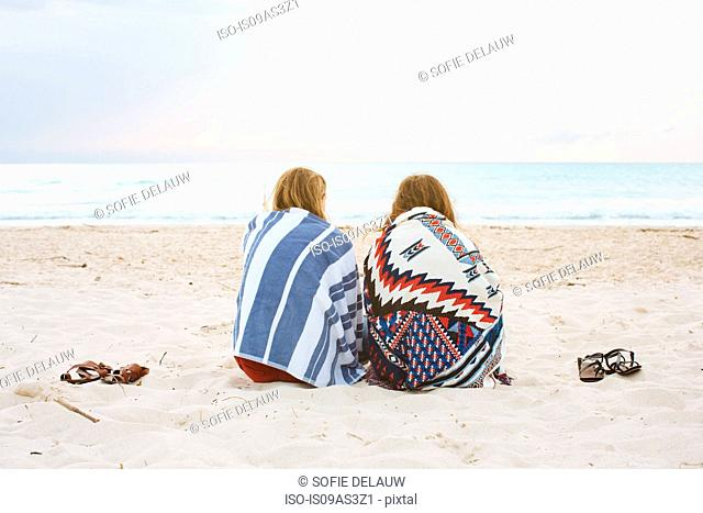 Rear view of two young female friends sitting on beach looking out to sea