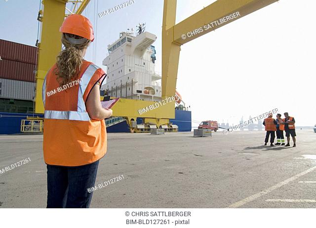 Woman wearing hard hat holding clipboard standing on dockside