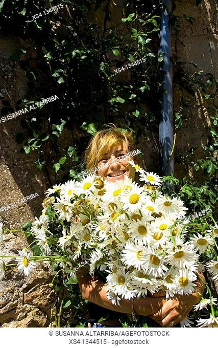Lady smiling behind a huge bouquet of daisies