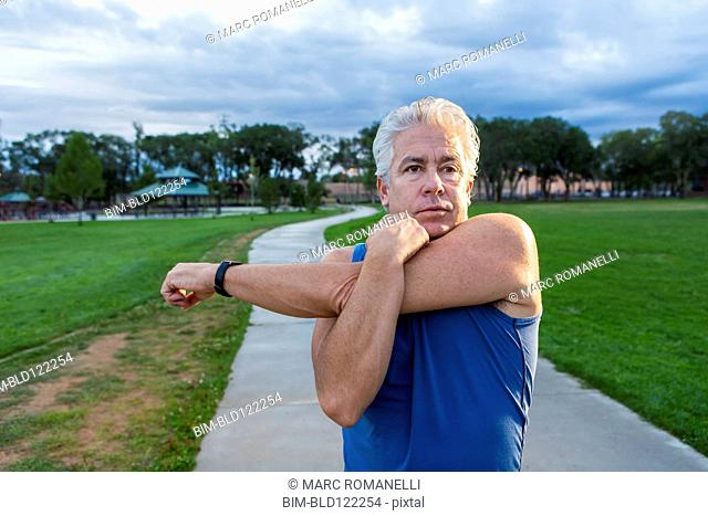 Hispanic man stretching in park