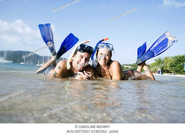 Portrait of a mid adult couple lying on the beach and smiling