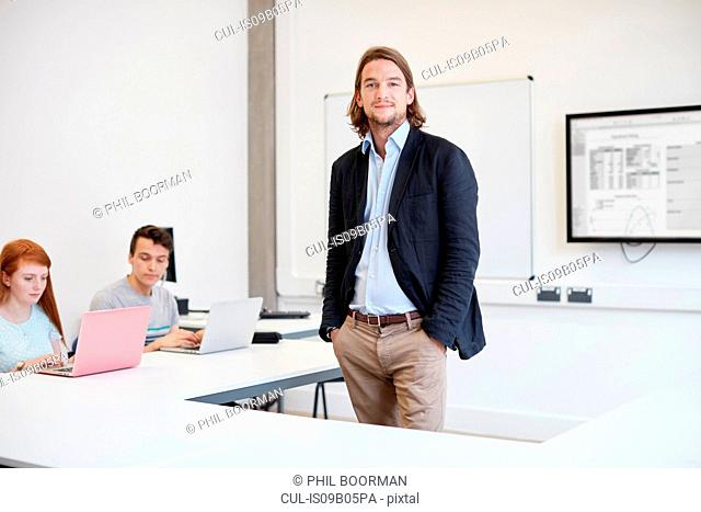 Portrait of male lecturer in higher education college classroom