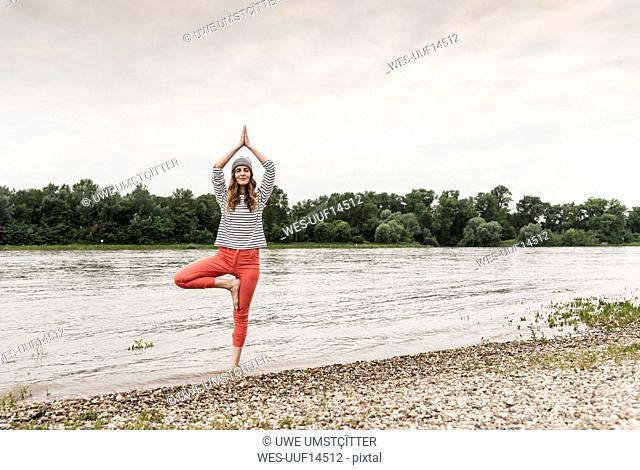 Woman practicing yoga in a river