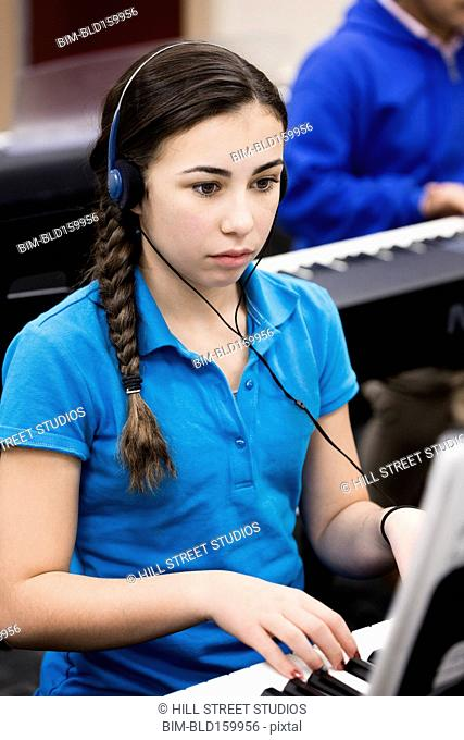 Caucasian student with headphones practicing keyboard in band class
