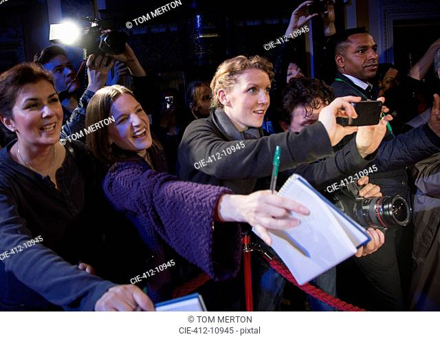 Fans reaching for autographs at red carpet event