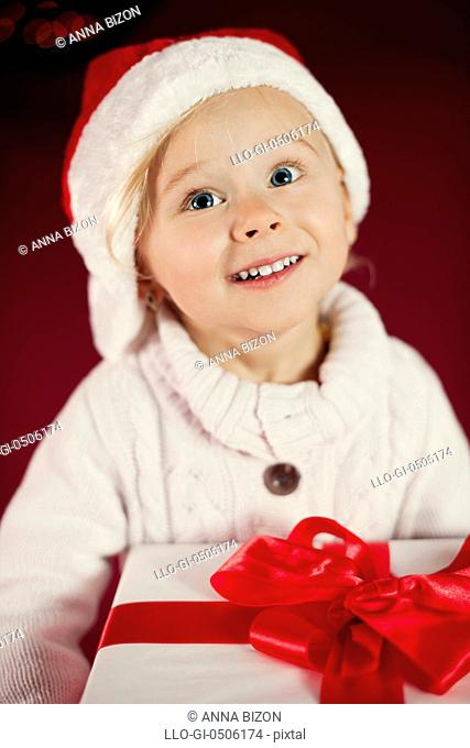 Cute girl with Santa hat holding Christmas gift, Debica, Poland