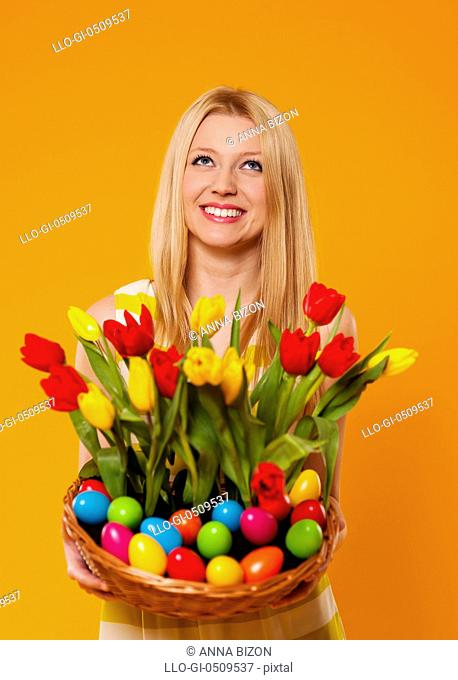 Happy woman holding basket with spring flower and Easter eggs Debica, Poland