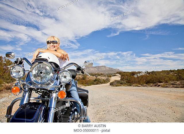 Senior woman in sunglasses poses on motorcycle on desert road