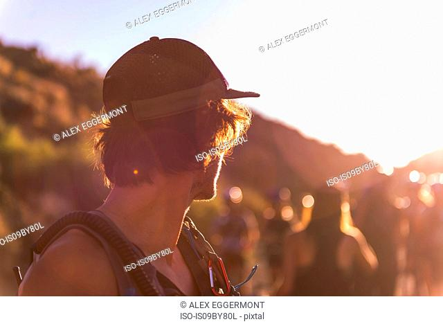 Man in baseball cap looking over his shoulder at group of people, sunset