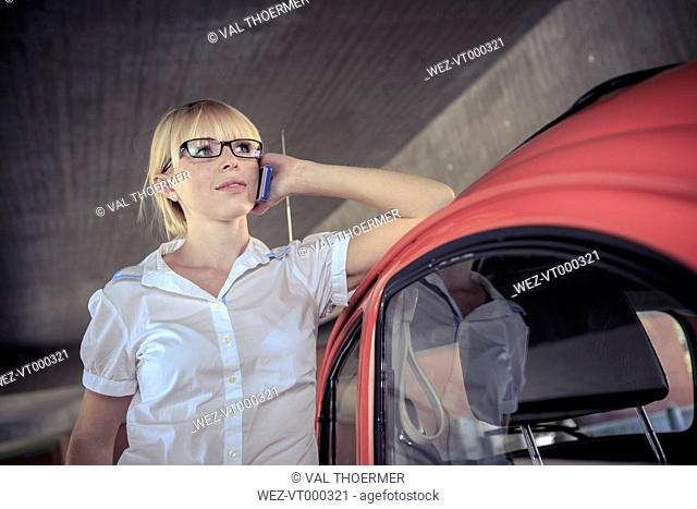 Portrait of young woman telephoning with smartphone leaning on car