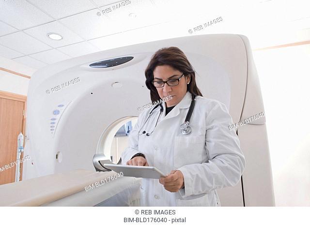 Hispanic doctor using digital tablet in MRI room