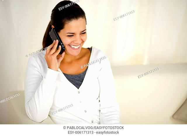 Portrait of a smiling young woman conversing on cellphone while is sitting on couch at home indoor