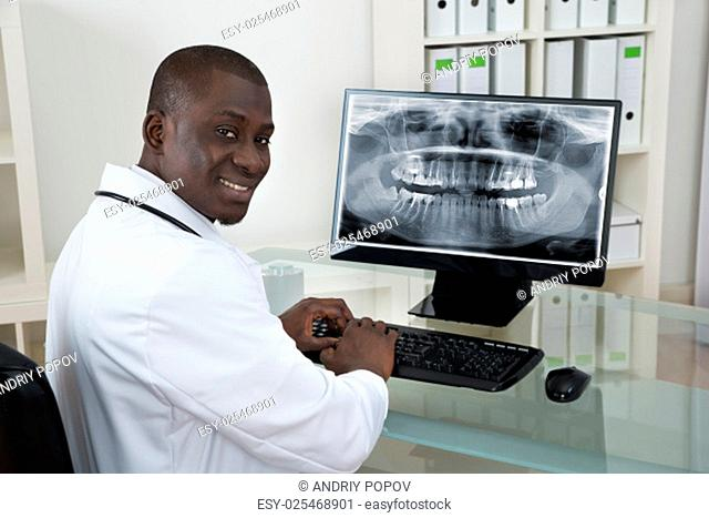 Young Happy African Dentist With Teeth X-ray On Computer At Desk
