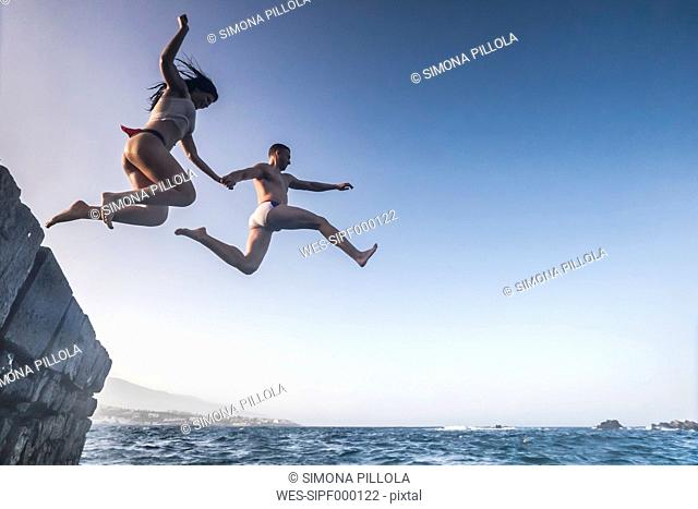 Spain, Tenerife, Young couple jumping from rock
