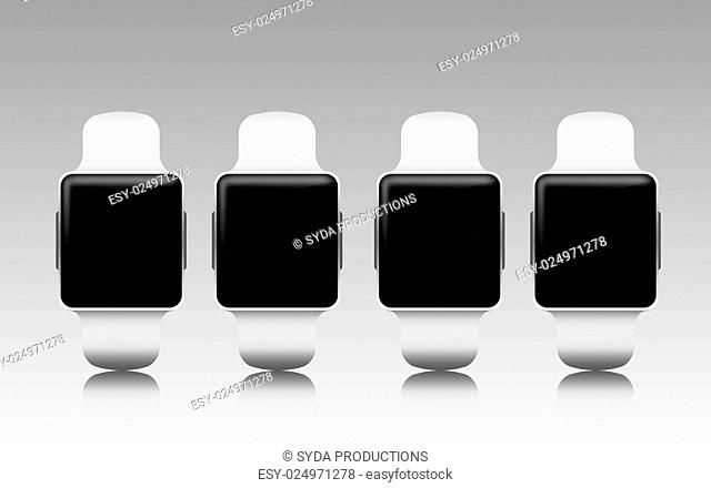 modern technology, object and media concept - smart watches set with black blank screen over gray background