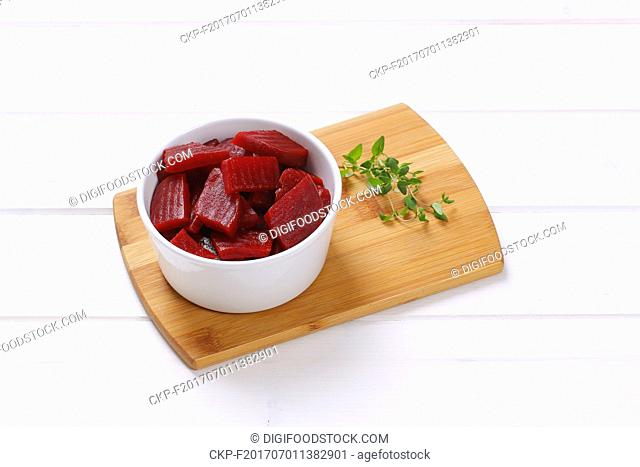 bowl of sliced and pickled beetroot on wooden cutting board