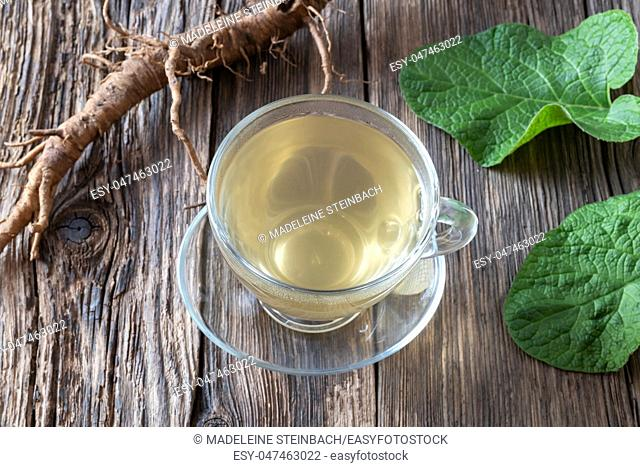 Burdock tea, root and leaves on a table