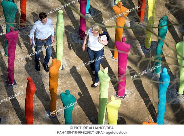 10 April 2018, Germany, Bad Iburg: Visitors walk through a group of sculptures in the run-up to the National Garden Show