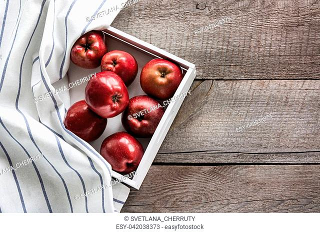 Ripe red apples in birch-box on wooden board with white striped napkin around and copy space for your recipe