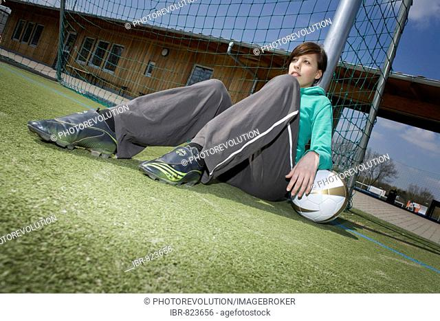 Young woman with a football leaning against a goal