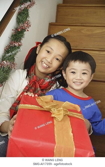 Girl and boy sitting on stairs, holding present, smiling at camera