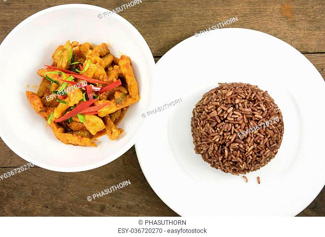 The delicious homemade Thai paneang curry food (pork peanut coconut cream curry or panang curry with pork) and cooked dark brown rice on the white plate on old...