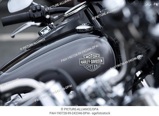 28 July 2019, Saxony, Dresden: Harley Davidson motorcycles stand side by side before the start of a biker parade on the occasion of the Harley Days Dresden 2019