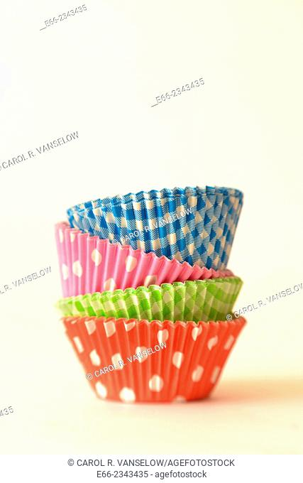 Stack of pastel coloured paper cup cake forms. Shot on light background. Shot with LensBaby for selective focus