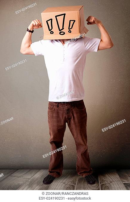 Young man gesturing with a cardboard box on his head with exclamation point