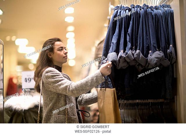 Young woman choosing clothes in shop