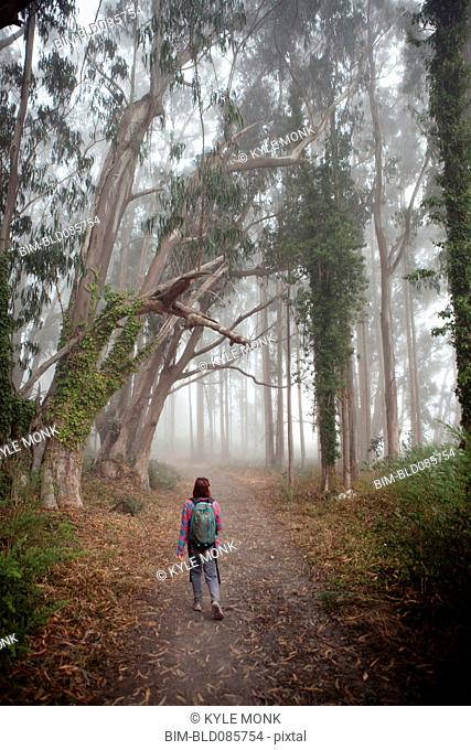 Korean woman in backpack walking in forest path