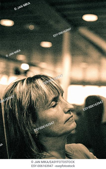 Closeup of middle aged woman sleeping in public transport. Toned grainy 35mm film scan