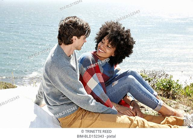 Couple sitting on picnic blanket at beach