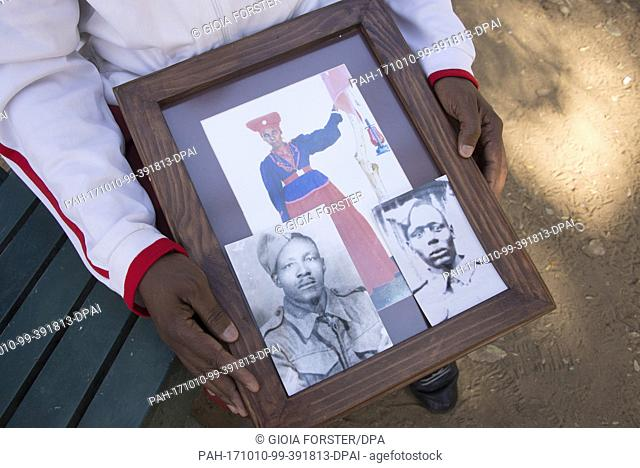 Uruanaani Scara Matundu, a representative of the Herero community, showing pictures of his ancestors in a park in Windhoek, Namibia, 12 May 2017