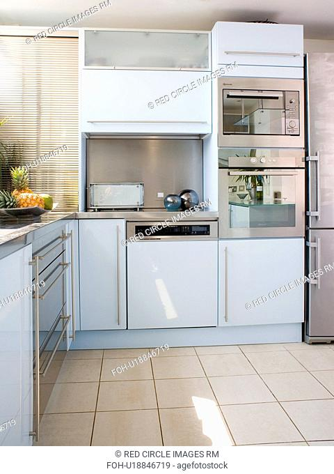 Stainless steel double oven in modern white kitchen with cream ceramic floor tiles
