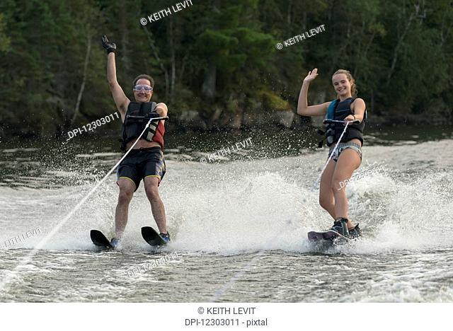 A father and daughter waterskiing side by side while waving to the camera; Ontario, Canada