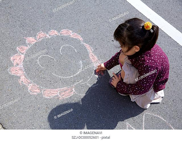 Girl drawing a picture with chalk