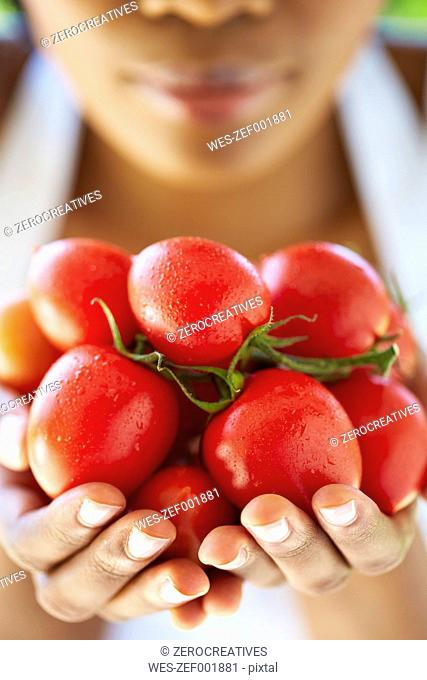 Woman's hands holding tomatoes